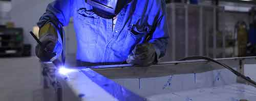mann i blå kjeledress som sveiser